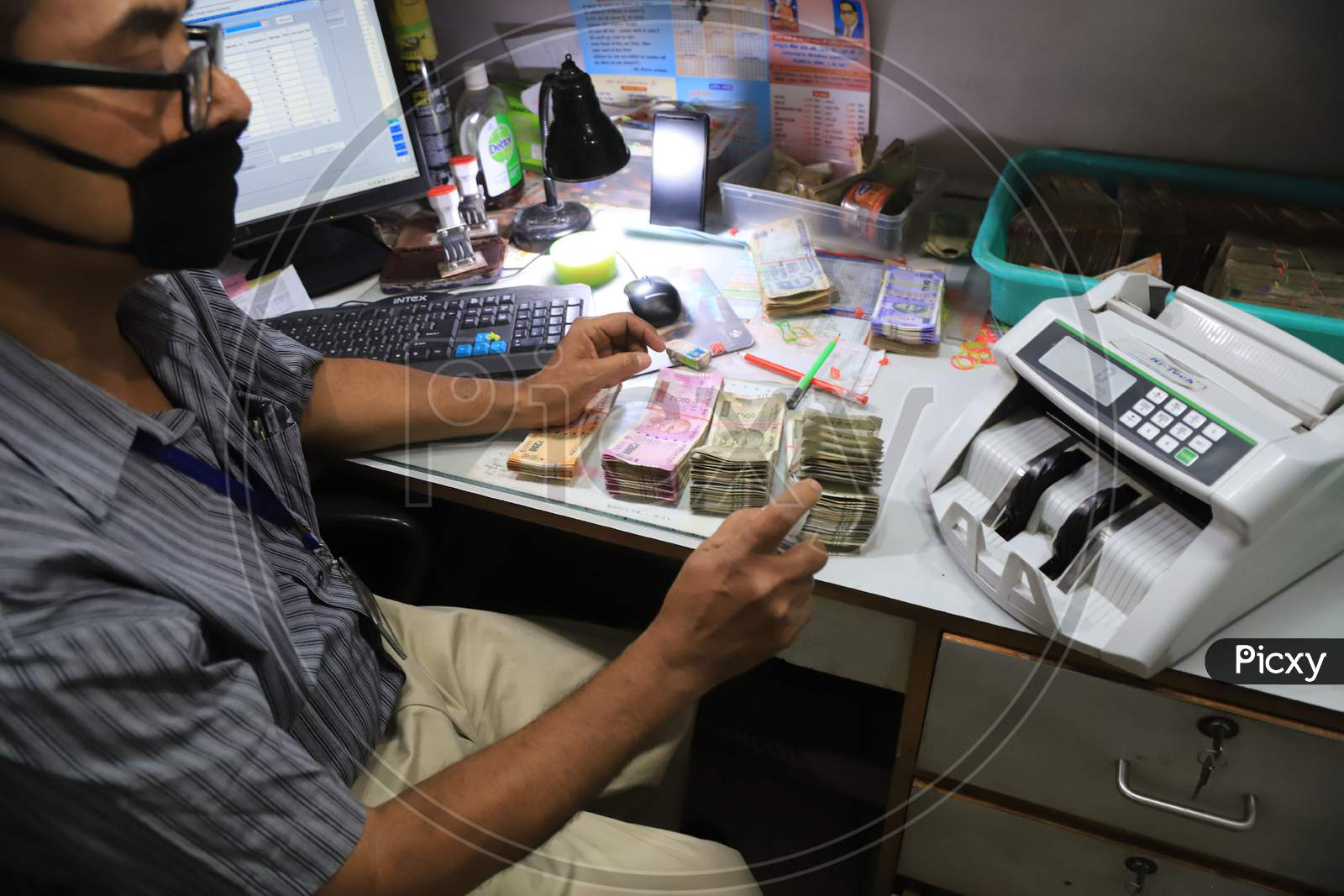 A Bank Employee Sanitize Indian Currency In Side A Bank During A Nationwide Lockdown To Slow The Spreading Of The Coronavirus Disease (Covid-19), In Prayagraj, April, 17, 2020.