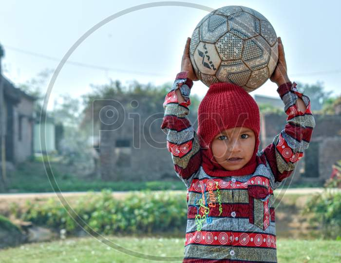 A 4-year-old poor child of a village is playing with a football