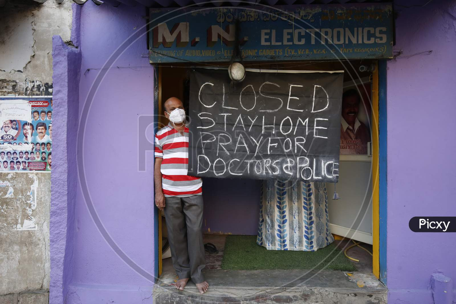 A Shopkeeper With A Shop Closed Board And Stay Home Slogan On It During Corona Virus ( Covid-19) Pandemic Lockdown In Bengaluru