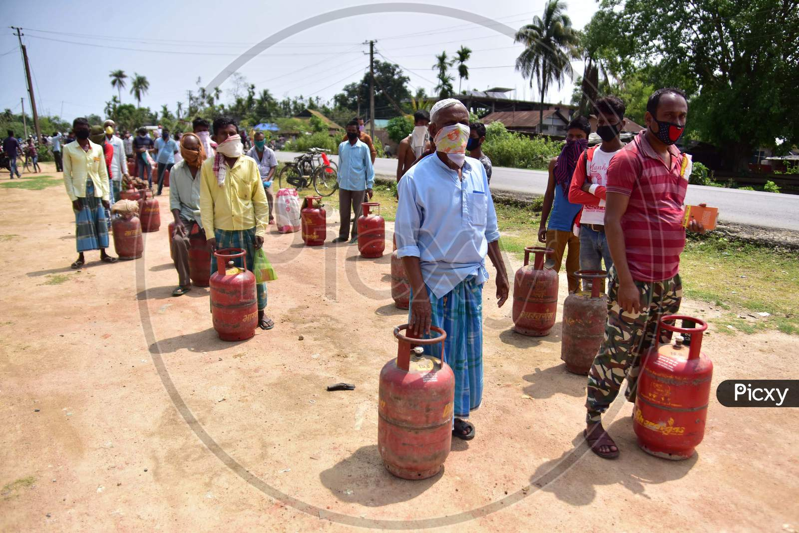 People Maintain Social Distance As They Wait In A Queue  To Collect  Lpg Gas Cylinder  During A Nationwide Lockdown In The Wake Of Coronavirus (Covid-19)  Pandemic, At Samaguri In Nagaon District Of Assam On  Tuesday, April 21, 2020