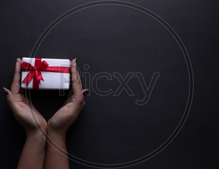 White gift box with red ribbon, black background flat lay for stock image