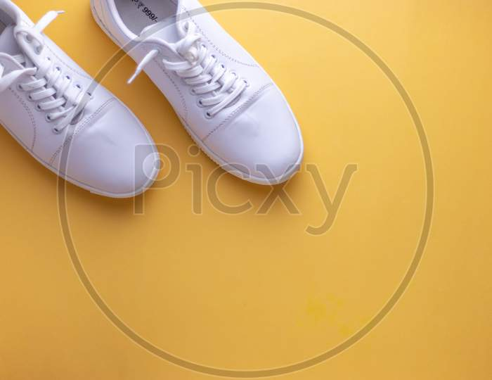 White sneakers on yellow colour background, flat lay top view minimal background.