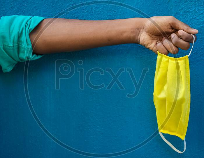 Man Holding Protective Yellow Face Mask Holding On His Hand Isolated On Blue Background