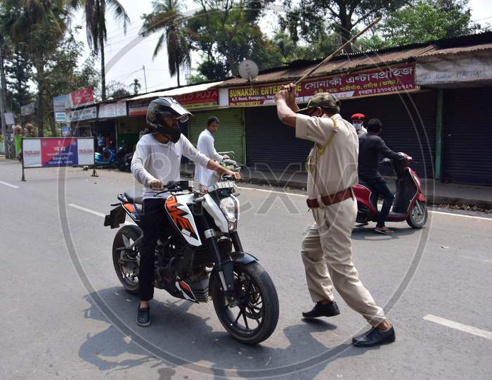 A Police Officer Wields His Baton Against A Man As A Punishment For Breaking The Lockdown Rules After India Ordered A 21-Day Nationwide Lockdown To Limit The Spreading Of Coronavirus Disease (Covid-19)  In Nagaon District Of Assam On Mar 26,2020