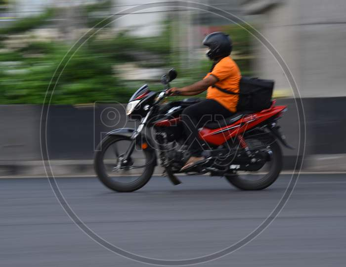 A swiggy delivery boy moves on his vehicle during nationwide lockdown amid coronavirus pandemic, April 8,2020, Hyderabad.
