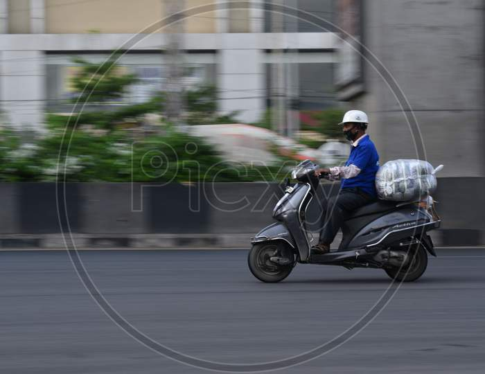 a man delivers essential groceries on his bike during nationwide lockdown amid coronavirus pandemic, April 8,2020, Hyderabad.