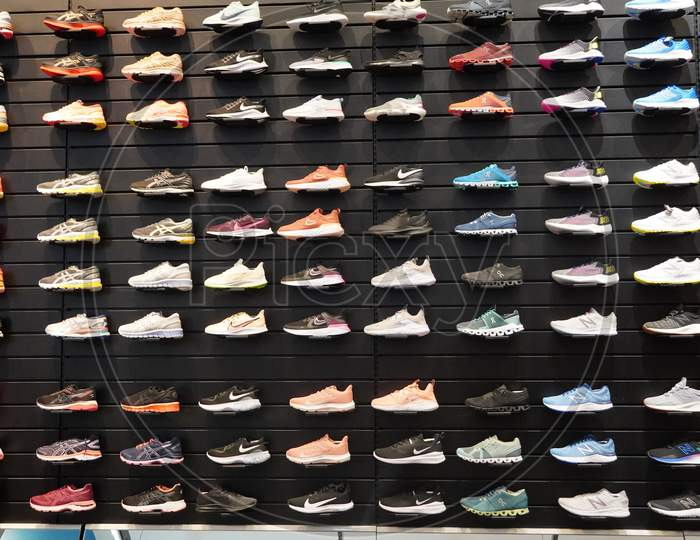 Shop Display Of A Lot Of Sports Shoes On A Wall. A View Of A Wall Of Shoes Inside The Store. Modern New Stylish Sneakers Running Shoes For Men And Women.