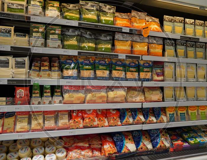 Different Types Of Cheese On Shelves In A Grocery Store. Shelf Of Packaged Products, Butter And Cheese At A Market. Cheddar, Edam, Mozzarella, Gouda, Blue Cheese.