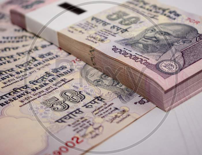 A bundle of 50 rupees notes put on the Indian currency 50 rupees notes on a white background