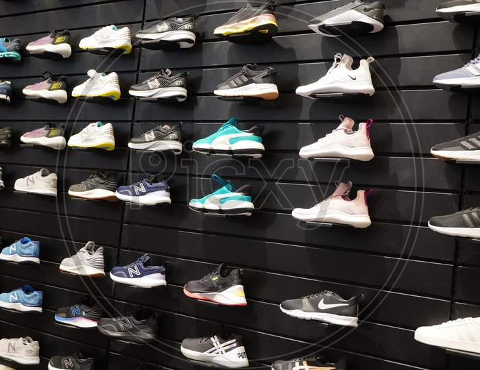 Shop Display Of A Lot Of Sports Shoes On A Wall. A View Of A Wall Of Shoes Inside The Store. Modern New Stylish Sneakers Running Shoes For Men And Women