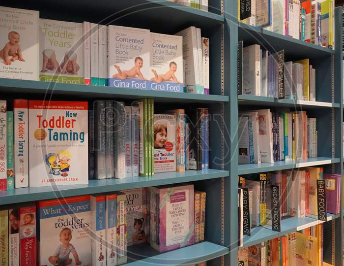 Bookshelf In Library With Many Parenting Books For Sale. Parenting, Toddler Guidebooks. Children Books. Toddler Books. What To Expect When You Are Expecting. Pregnancy Guide -