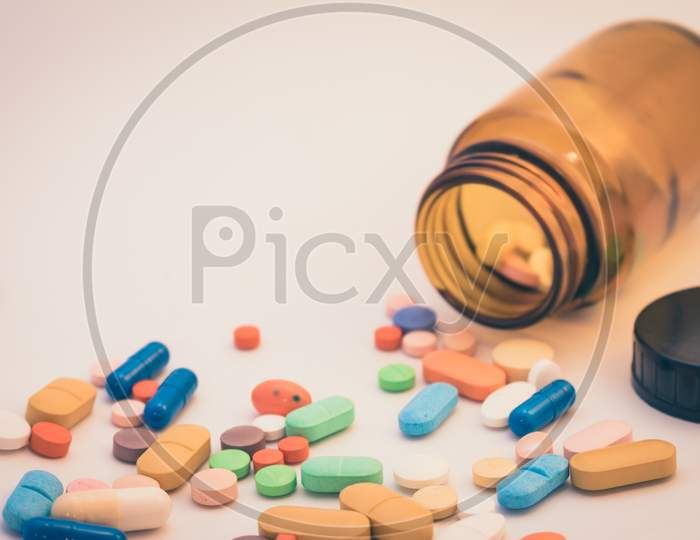 Brown Glass Bottle With Pills Of Various Colors. Drugs For Use In Humans. Pills On White Background.