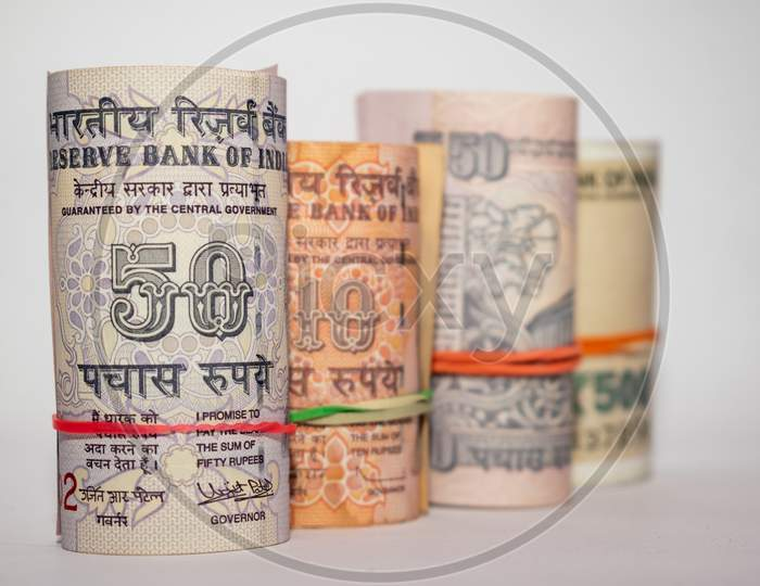 Rolls and bundles of Indian currency notes placed on a white background