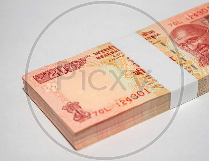 Bundle of indian currency notes of twenty rupees on white background