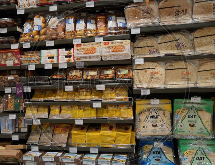 Different Fresh Bread On The Shelves In Bakery. Interior Of A Modern Grocery Store Showcasing The Bread Aisle With A Variety Of Prepackaged Breads Available.