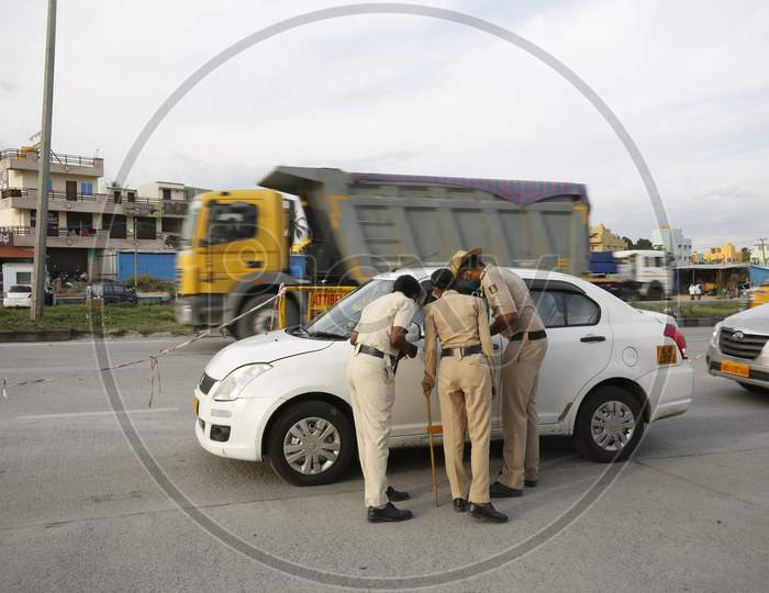 Police personnel check papers of people travelling at a check post during the nationwide lockdown to stop the spread of coronavirus (Covid-19) in Bangalore, India.