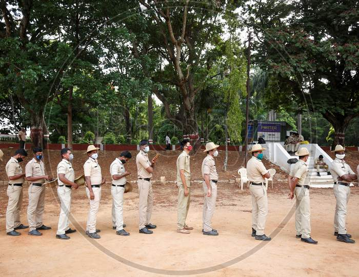 Police personnel stand in a queue to check for covid-19 during a health screening camp for the police forces in Bangalore, India.