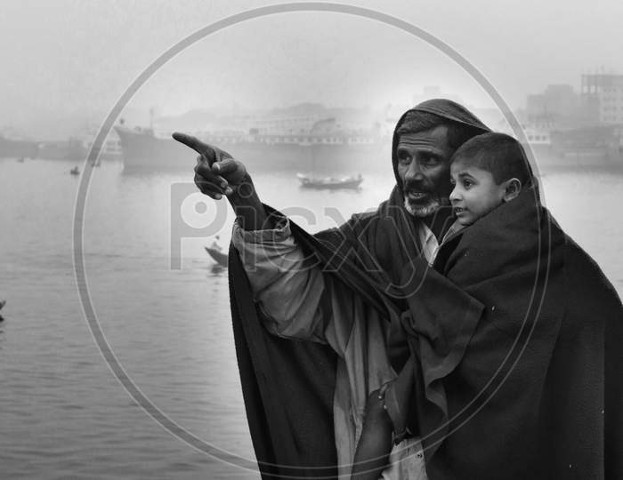 Bangladesh – January 06, 2014: A Boy And His Father Watching The Winter River With The Full Body Of Wearing A Thick Blanket On A Winter Morning.