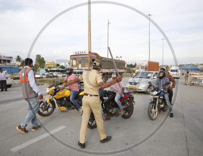 A police officer wields his baton at a check post during the nationwide lockdown to stop the spread of coronavirus (Covid-19) in Bangalore, India.