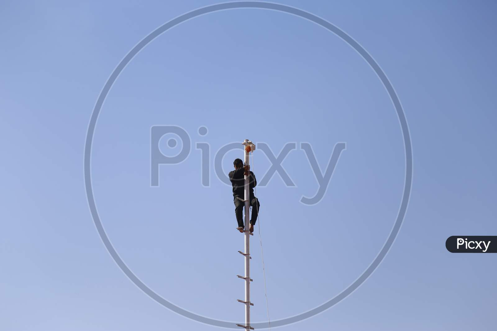 A Man Standing On Pole In Nagaur Cattle Fair