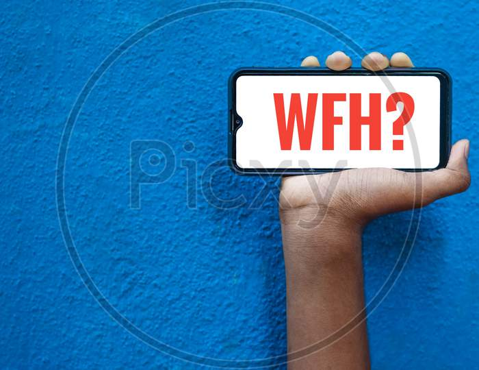 Wfh - Work From Home Word On Smart Phone Screen Isolated On Blue Background With Copy Space For Text. Person Holding Mobile On His Hand And Showing Front Of The Screen Concept Wfh.