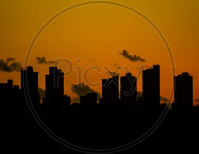 Huge Buildings Of A City During Sunset. Warm Colors Due To The Sun'S Fall.