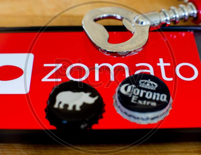 Mobile Phone Showing Zomato On A Wooden Platform With Beer Bottle Caps And An Opener On The Side