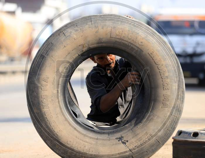 A Man Repairing Truck Tyre  at a Road Side Shop  During Extended Nationwide Lockdown Amidst Coronavirus Or COVID-19 Pandemic in Prayagraj