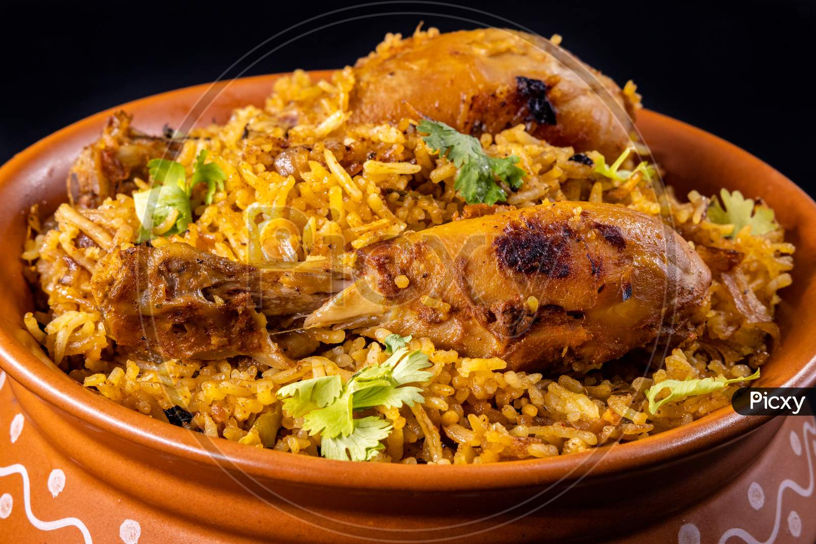 Hyderabadi Chicken Dum Biryani Beautifully Served In A Authentic Clay Bowl Over An Isolated Black Background