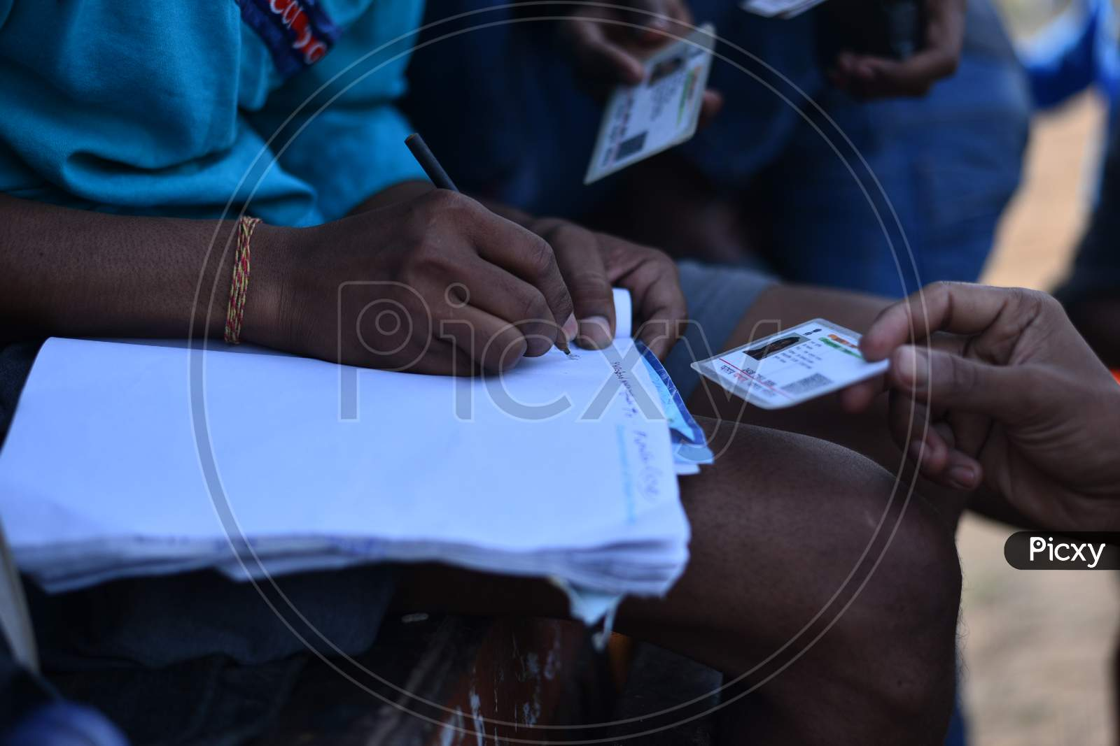 Migrant Workers From West Bengal And Bihar Write Down Their Aadhar Details In A Paper As They Wait For Permission To Cross Telangana State At A Checkpost In Aswaropeta During An Extended Lockdown Amid Coronavirus Fears, May 16,2020.