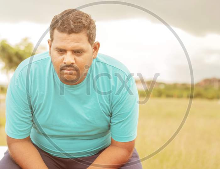 Seriously Fat Man On Outdoor, Park - Concept Of Sadness Due Overweight - Indian Obese Man Feeling Unhappy Or Depressed.