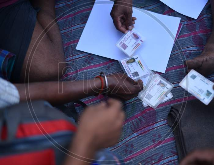 Migrant workers hold their Aadhar Cards to register at Telangana Border to get permission to move till their hometown in Bihar, Aswaraopet, Telangana, May 16,2020