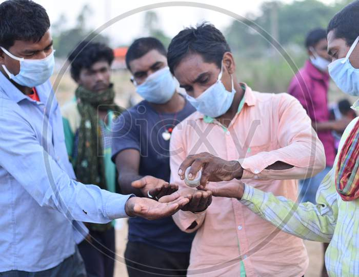 Migrant workers sanitize their hands as they wait at TS-AP Border to get a permission letter to travel across states to reach their hometown in Bihar, May 16,2020, Aswaraopet, Telangana