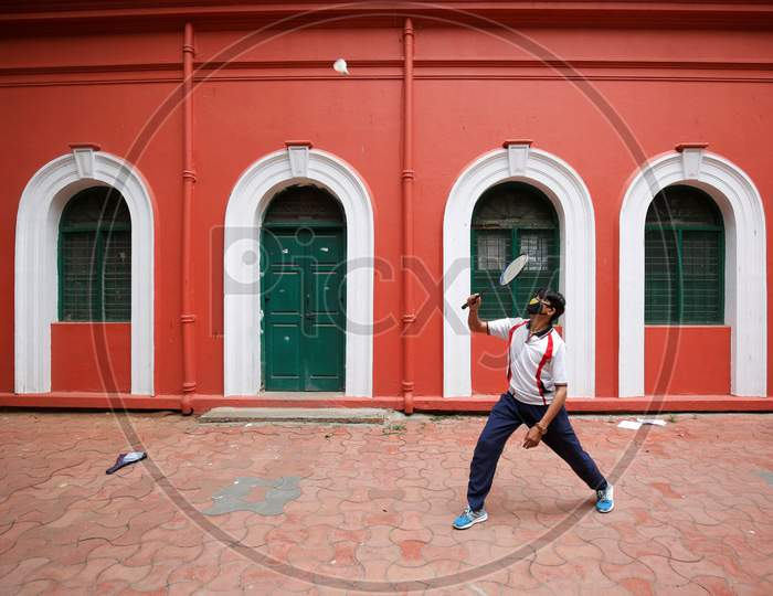 A man plays badminton outside a government building after the state eased lockdown norms during the nationwide lockdown to prevent the spread of coronavirus (COVID-19) in Bangalore, India.
