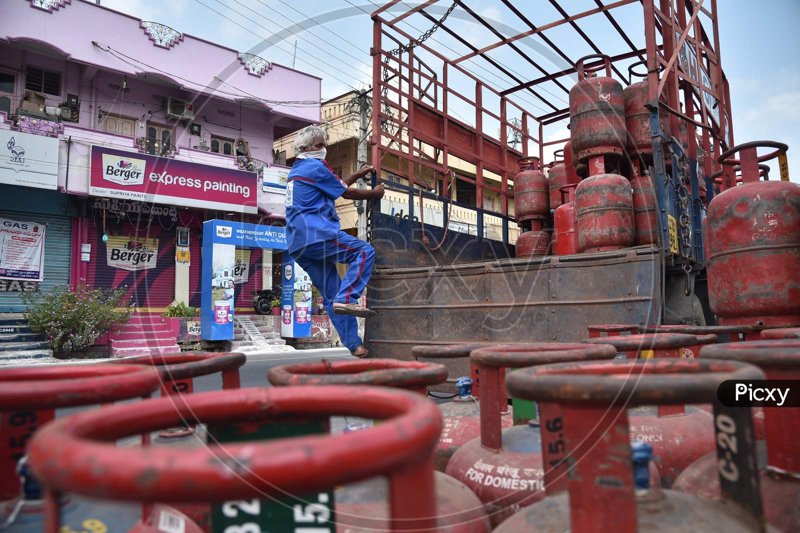 A Worker Gets Down From A Vehicle Loaded With Lpg Cylinders During The Nationwide Lockdown Imposed In The Wake Of Coronavirus, In Vijayawada.