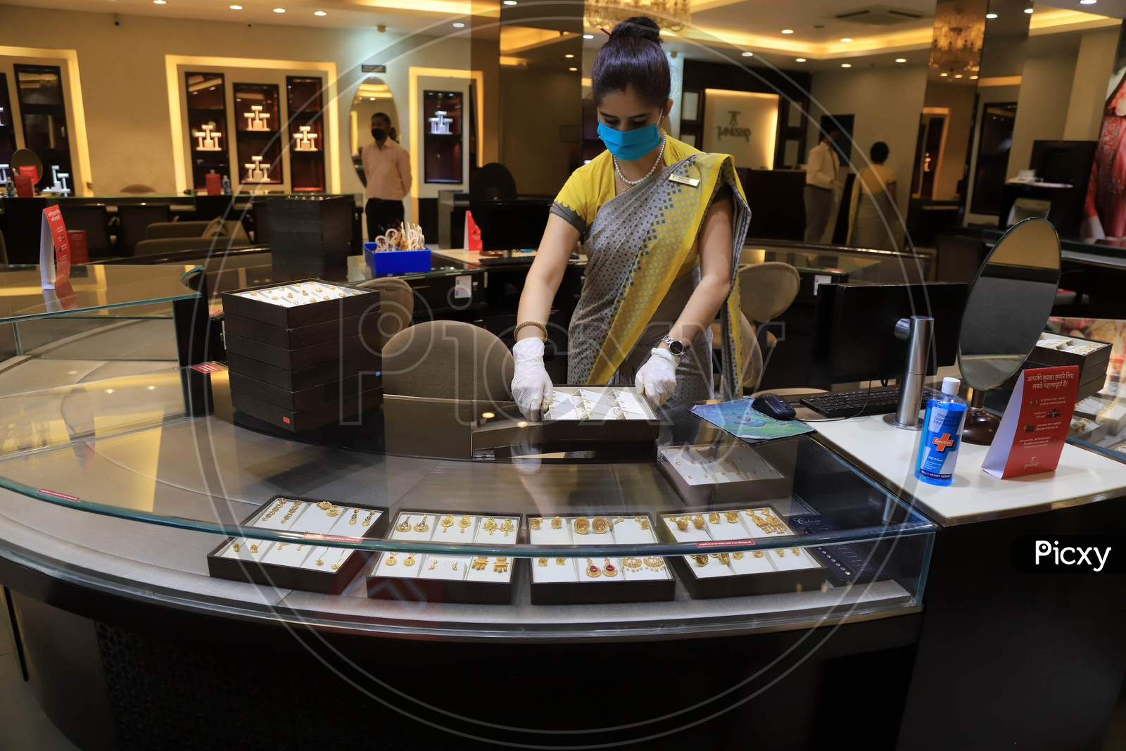 A Sales Girl Arranges Jewellery At A Shop After  Authorities Allowed Shopkeepers To Open Their Establishments With Certain Restrictions During Coronavirus Or Covid-19 Pandemic In Prayagraj, May 20,2020