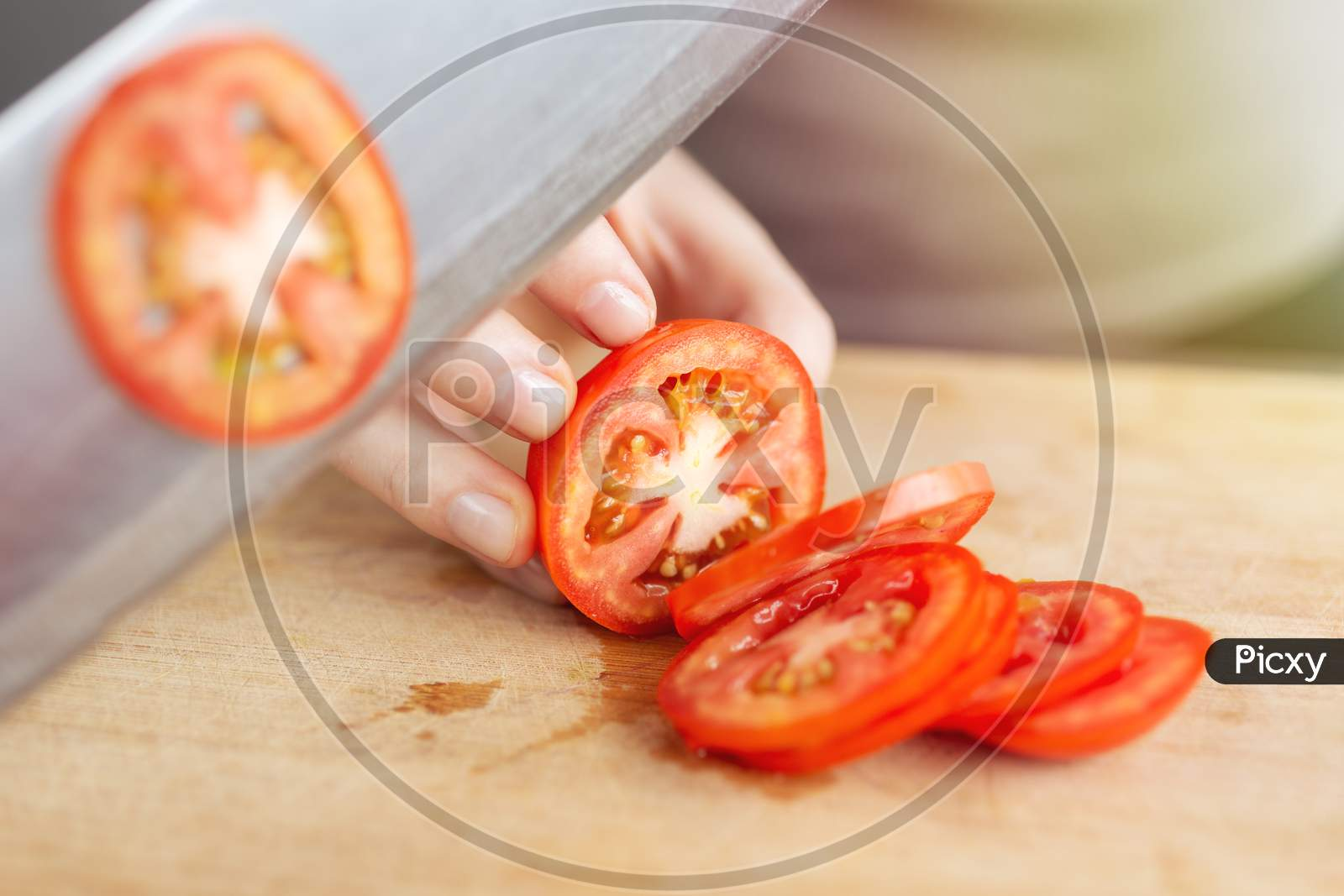 Close Up Of Red Ripe Tomato Cutting With A Knife. Healthy Food Preparation Concept