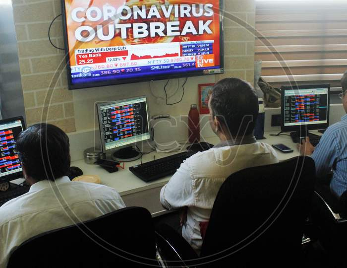 Brokers work at their computer terminal at a stock brokerage firm following the coronavirus outbreak, in Mumbai, India on March 12, 2020.