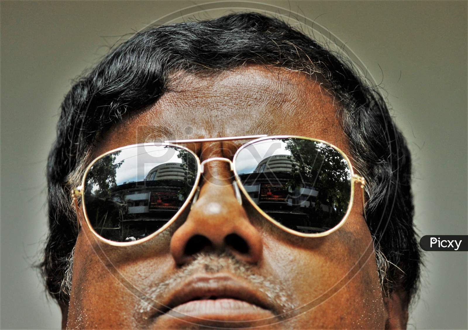 The Bombay Stock Exchange (BSE) building is reflected in the glasses of a man as he watches the Sensex results following the coronavirus outbreak, on the large screen outside the facade of the building in Mumbai, March 12, 2020.