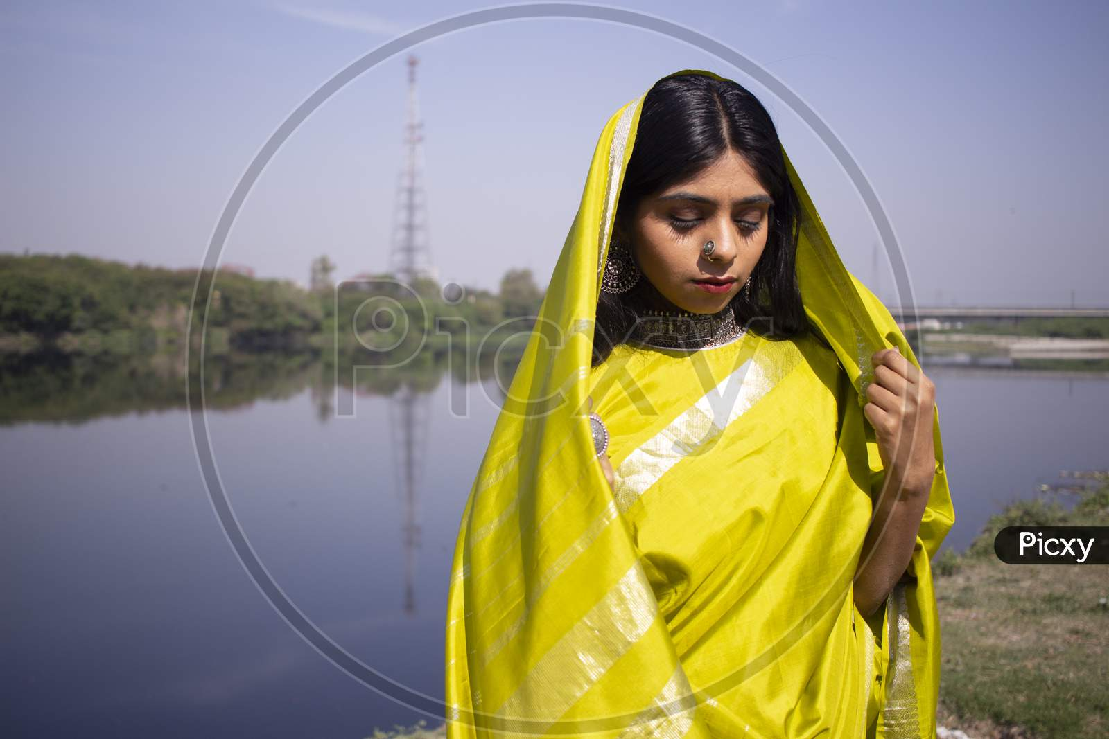 Indian Girl Wearing Green Saree Standing In A Landscape