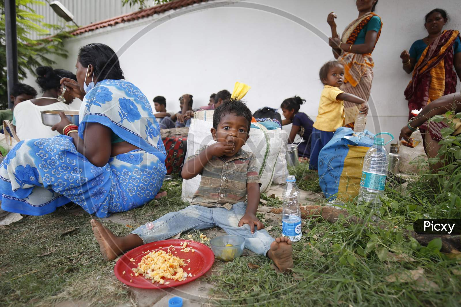 The child of a migrant workers eats his lunch on a pavement before boarding a bus to be taken to a government-arranged train to his destination after the state eased lockdown regulations during the extended nationwide lockdown to prevent the spread of coronavirus (Covid-19) in Bangalore, India.