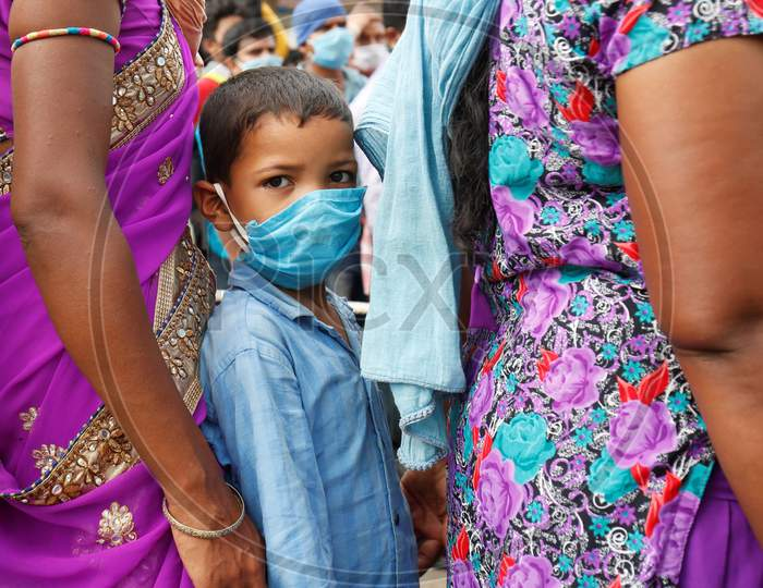 A boy waits for a health screening before boarding a bus to be taken to a government-arranged train to his destination after the state eased lockdown regulations during the extended nationwide lockdown to prevent the spread of coronavirus (Covid-19) in Bangalore, India.