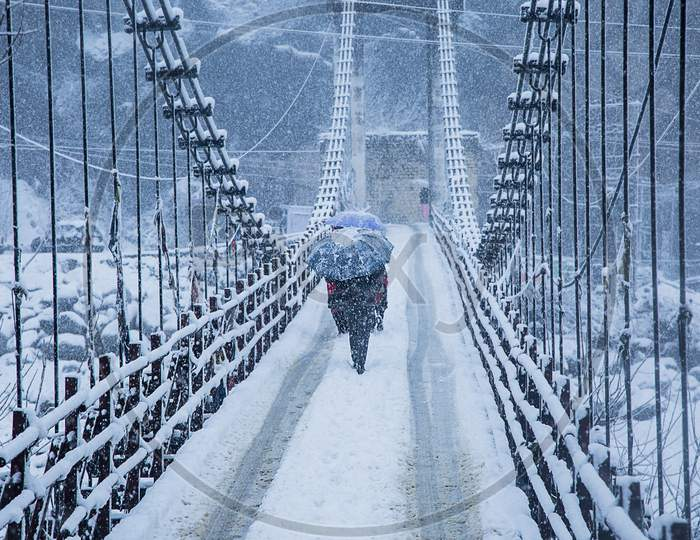 Heavy Winter Snow Fall, A Person Walking Alone With Black Umbrella On The Bridge, Wide Angle Shot - Image