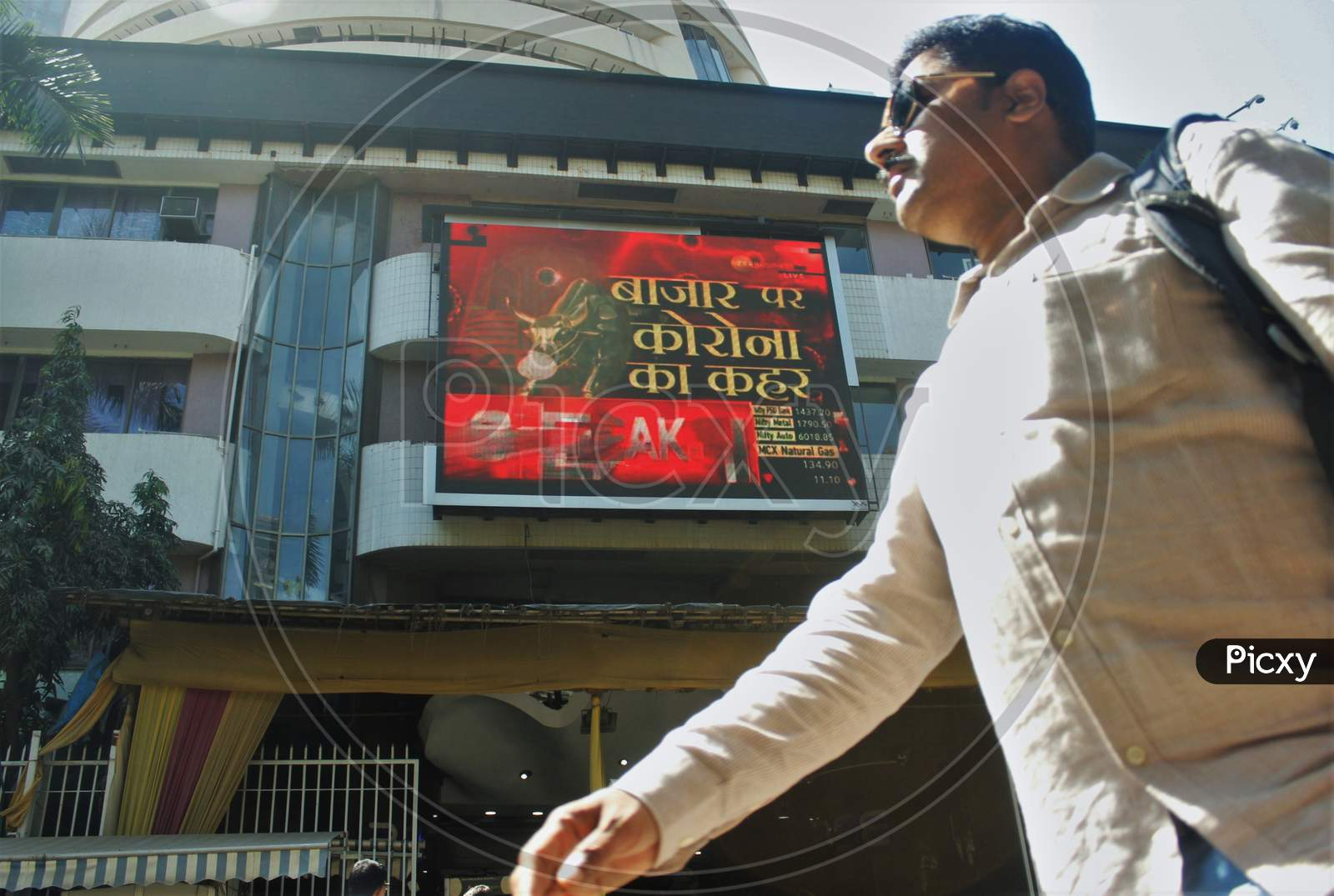 A man walks past a screen displaying the current market situation amid coronavirus outbreak, on the facade of the Bombay Stock Exchange (BSE) , in Mumbai, India, on March 12, 2020.