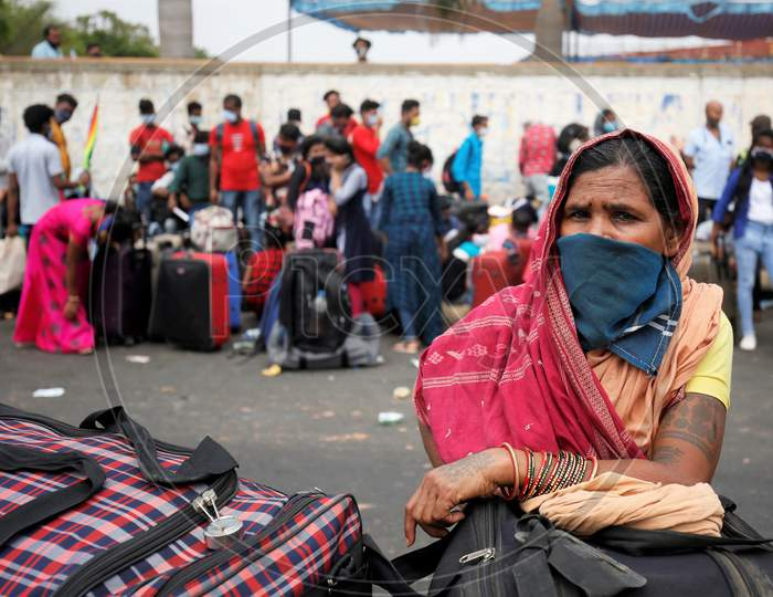A woman waits for a health screening before boarding a bus to be taken to a government-arranged train to her destination after the state eased lockdown regulations during the extended nationwide lockdown to prevent the spread of coronavirus (Covid-19) in Bangalore, India.