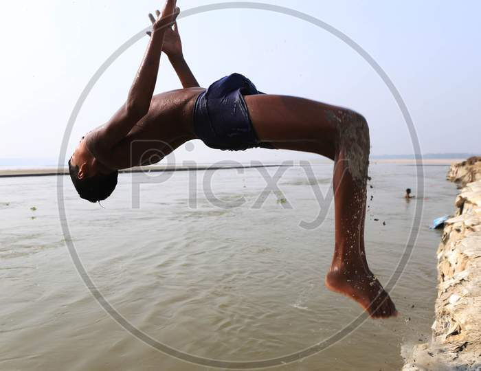 A Boy Jumping and Taking bath  In Triveni Sangam River on a Hot Summer Day During Extended Nationwide Lockdown Amidst Coronavirus Or COVID-19 Pandemic in Prayagraj, May 24,2020