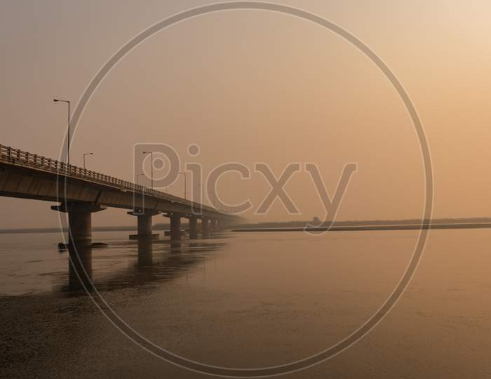 Road Bridge Over River With Its Water Reflection At Dawn From Low Angle