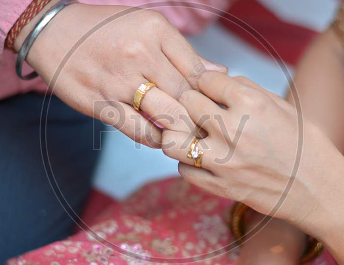 Bride and groom exchange engagement ring in Indian Hindu wedding.