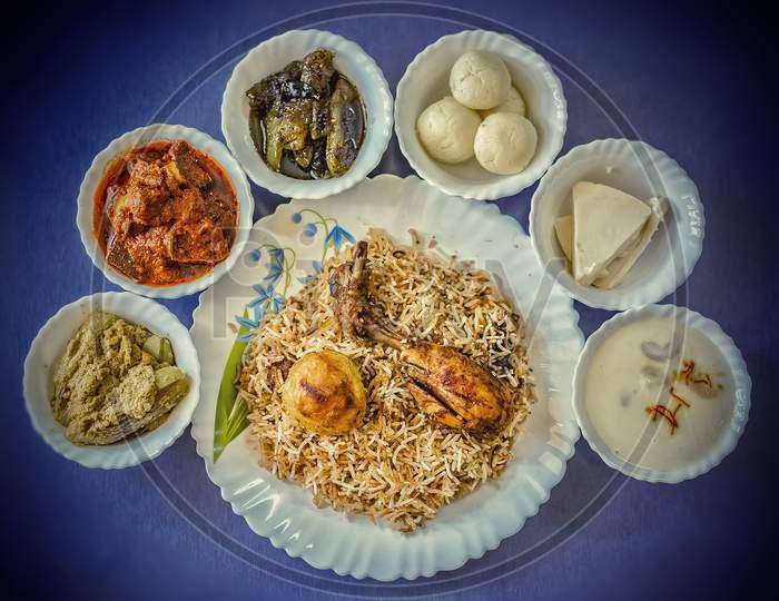 Chicken Biryani Served With Sweet Dishes And Raita