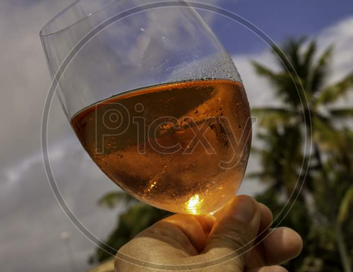 Crystal Glass With Rose Wine In A Toast Attitude. High Class Concept. Refreshing Alcoholic Drink Made With Grapes.